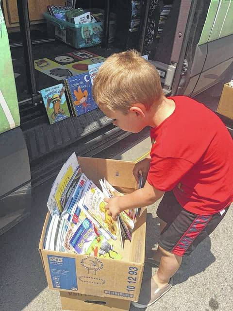 Photo courtesy of Tina Schneider A boy looks through a box filled with books for something that catches his eye.